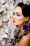 Floral face art with anemone in jewelry, sensual young brunette woman Stock Photos