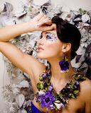Floral face art with anemone in jewelry, sensual young brunette woman Royalty Free Stock Images
