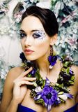 Floral face art with anemone in jewelry, sensual young brunette woman in studio close up. 8 march concept stock photography