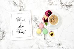 Floral flat lay Tablet PC coffee cookies pansy flowers. Floral flat lay. Tablet PC, coffee, french cookies macaroons, pansy flowers Royalty Free Stock Images