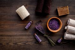 Floral foot spa with lavender. Spa salt, sponge, soap, towel on dark wooden background top view copyspace Stock Images