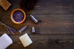 Floral foot spa with lavender. Spa salt, sponge, soap, towel on dark wooden background top view copyspace Royalty Free Stock Photography