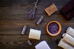 Floral foot spa with lavender. Spa salt, sponge, soap, towel on dark wooden background top view copyspace Stock Photos