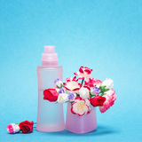 Floral fragrance. Pink glass perfume bottle and bouquet of small paper flowers in its cap on blue background. Copy space Stock Photo