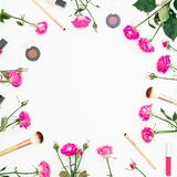 Floral frame with feminine composition with pink roses and cosmetics on white background. Beauty concept. Flat lay, Top view. Royalty Free Stock Images