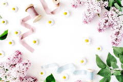 Floral frame with lilac flower, chamomile, fresh branches and spool with blue and beige ribbon isolated on white background. Flat lay, top view Stock Images