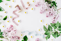 Floral frame with lilac flower, chamomile, fresh branches and spool with blue and beige ribbon isolated on white background. Flat lay, top view royalty free stock photography