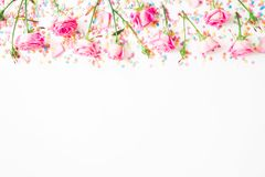 Floral frame made of pink flowers and bright candy confetti on white background. Flat lay, Top view. Roses flower texture. Floral frame made of pink flowers and royalty free stock image