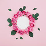 Floral frame made of white blank, pink rose flowers and green leaves on pastel background top view. Flat lay styling. Fashion and creative composition Stock Images
