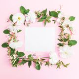 Floral frame made of white flowers and paper card on pink background. Floral background. Flat lay, top view. Stock Photos