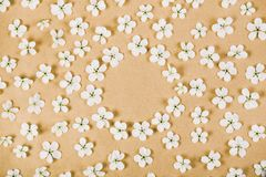 Floral frame made of white spring flowers on brown paper background. Flat lay. Top view stock images