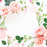 Floral frame of pink roses, buds and leaves on white background. Flat lay, top view. Floral background. Royalty Free Stock Photos