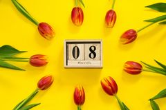 Floral frame with red tulip flowers around wooden cubic calendar with date of 8 march. International women`s day composition from royalty free stock photo