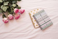 Floral frame with stunning pink roses and notebooks on pink bed sheets in the bedroom. Freelance workspace. Wedding, gift card, va royalty free stock photo