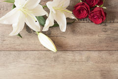 Floral frame with stunning white lilies and red roses on wooden background. Copy space. Wedding, gift card, valentine's day Royalty Free Stock Photos