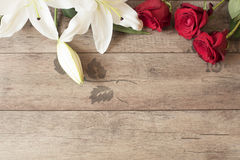 Floral frame with stunning white lilies and red roses on wooden background. Copy space. Wedding, gift card, valentine's day Royalty Free Stock Photo