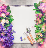Floral Gardening background with assortment of colorful garden flowers in pots , blank paper notebook and gardening tools, top vie stock photography
