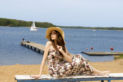 Floral girl with hat sitting on beach Stock Photos