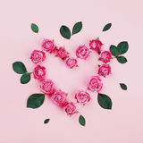 Floral heart made of pink rose flowers and green leaves on pastel background top view. Flat lay styling. Fashion composition. Floral heart made of pink rose Royalty Free Stock Photography