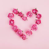 Floral heart made of pink rose flowers on pastel background top view. Flat lay styling. Fashion and creative composition. Royalty Free Stock Photos