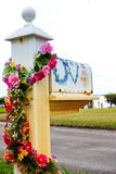 Floral Mailbox. Old outdoor mailbox decorated with strands of flowers and the word LOVE painted on box on coastal area of Florida Stock Image
