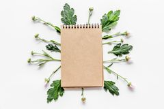 Floral mockup. Notebook among buds and leaves on white background top view Royalty Free Stock Photo
