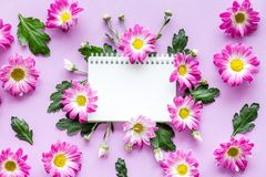 Floral mockup. Notebook among pink flowers on purple background top view Stock Image