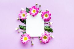 Floral mockup. Sheet of paper in frame of pink flowers on purple background top view Royalty Free Stock Photos