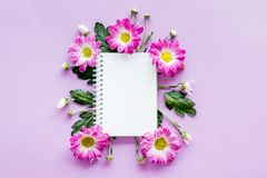 Floral mockup. Sheet of paper in frame of pink flowers on purple background top view.  Royalty Free Stock Photo