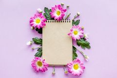 Floral mockup. Sheet of paper in frame of pink flowers on purple background top view.  Stock Photos