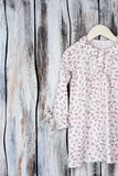 Floral nightgown for young girls. On wooden background. Long sleeve and ruffle collar. Sleeping garment on wooden hanger Royalty Free Stock Photography