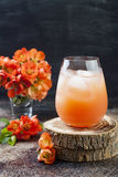 Floral pastel peach and pink brunch cocktail garnished with quince flowers over old rustic background.  Royalty Free Stock Image