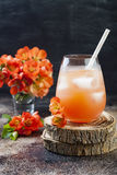 Floral pastel peach and pink brunch cocktail garnished with quince flowers over old rustic background.  Royalty Free Stock Photo