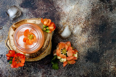 Floral pastel peach and pink brunch cocktail garnished with quince flowers over old rustic background. Top view, flat lay, copy space Royalty Free Stock Photos