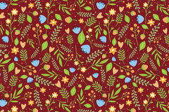 Floral pattern with blue flowers and orange berries. Seamless floral pattern with orange and blue flowers and green leaves on reddish brown background Royalty Free Stock Images