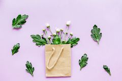 Floral pattern. Bouquet in a paper bag on purple background top view Royalty Free Stock Photography