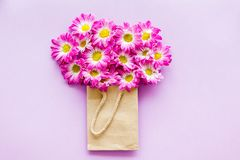 Floral pattern. Bouquet in a paper bag on purple background top view copyspace Stock Photography