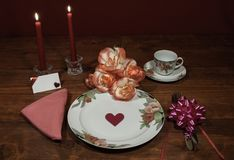 Floral pattern fine china dinnerware with matching plate, cup and saucer. bouquet of orange and white roses, pink napkin, silverwa. Re, red candles and card royalty free stock photo