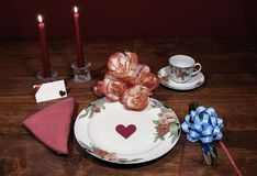 Floral pattern fine china dinnerware with matching plate, cup and saucer. bouquet of orange and white rpses, pink napkin, silverwa. Re, red candles and card royalty free stock image