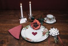 Floral pattern fine china dinnerware with matching plate, cup and saucer. pink rose, pink napkin, silverware, white candles and ca. Rd stock photo