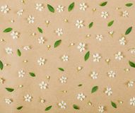 Floral pattern made of white spring flowers, buds and green leaves on brown paper background. Flat lay. Top view Stock Image