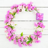 Floral pattern of pink flowers and ring box on white rustic background. Flat lay, top view. Floral frame concept Stock Photo