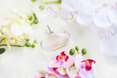 Floral perfume bottle with yellow, white and pink orchid flowers Stock Photo