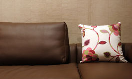 Floral pillow on a brown leather couch - home interiors Stock Photography