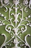 Floral plaster white ornament on warm green wall, abstract. Background Stock Photos
