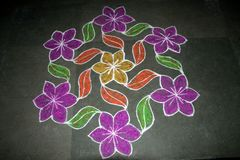 Floral Rangoli Design. Creation of flowers and leaves in Rangoli art using stone powder mixed with colour Royalty Free Stock Photography