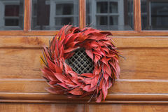 Floral red outdoor Christmas wreath hanging at entrance door Stock Photos