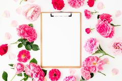 Floral round frame of pink roses with clipboard on white background. Flat lay, Top view. Royalty Free Stock Image