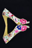 Floral shoes. Floral high heels shoes on a black background Stock Photos