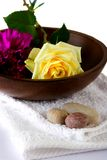 Floral spa therapy. Wooden bowl with white towel and scattered pebbles decorated with a white rose and magenta carnation, suitable for spa and healthcare Stock Image